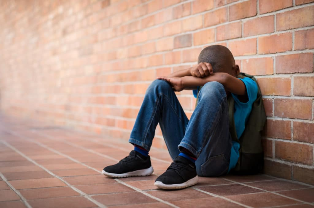 Young boy with his head in his harms leaning against a brick wall