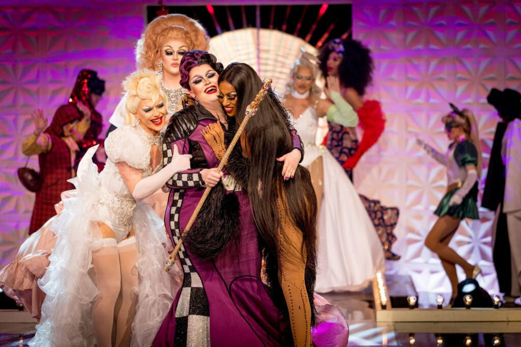 Drag queen Lawrence Chaney in the middle of a group hug of her fellow Drag Race UK finalists