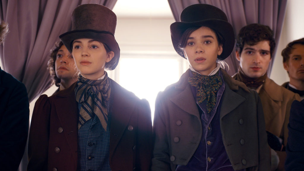 Ella Hunt and Hailee Steinfeld wearing top hats and period garbs in front of a window