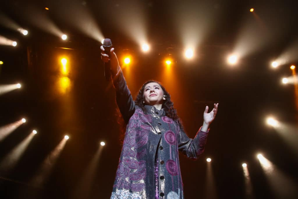 Manizha Sangin holds her microphone in the air against a constellation of spotlights