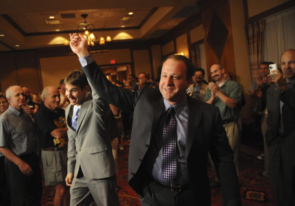 Jared Polis (R) and Marlon Reis hold hands as people clap behind them
