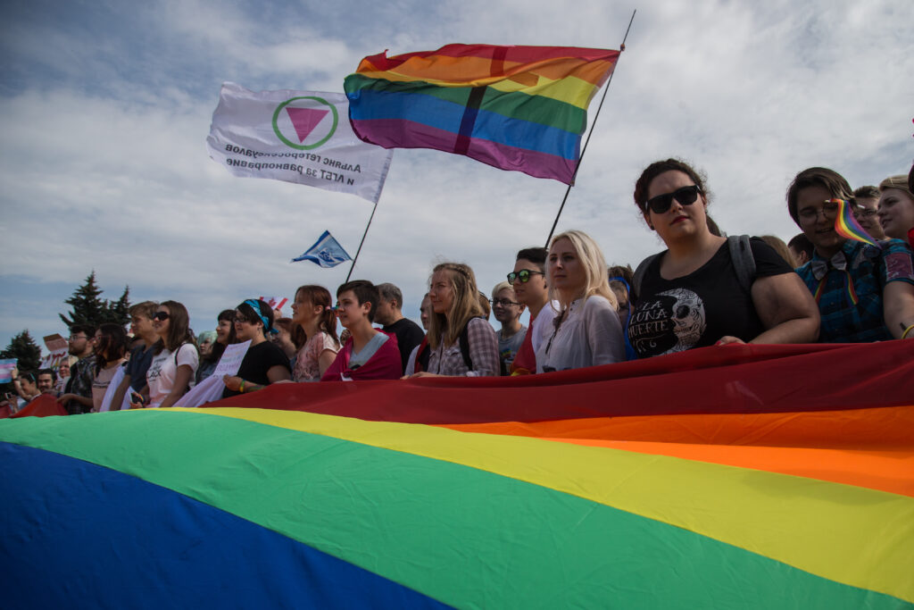 Members of the Alliance of Heterosexuals and LGBT for Equality, their flag on the left, at the St Petersburg LGBT+ Pride