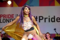 Sinitta dances as she holds her gold cape on the Pride in London main stage