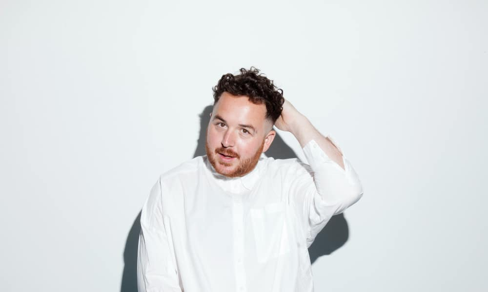 Scottee with his hand behind his head in a white shirt against a white background