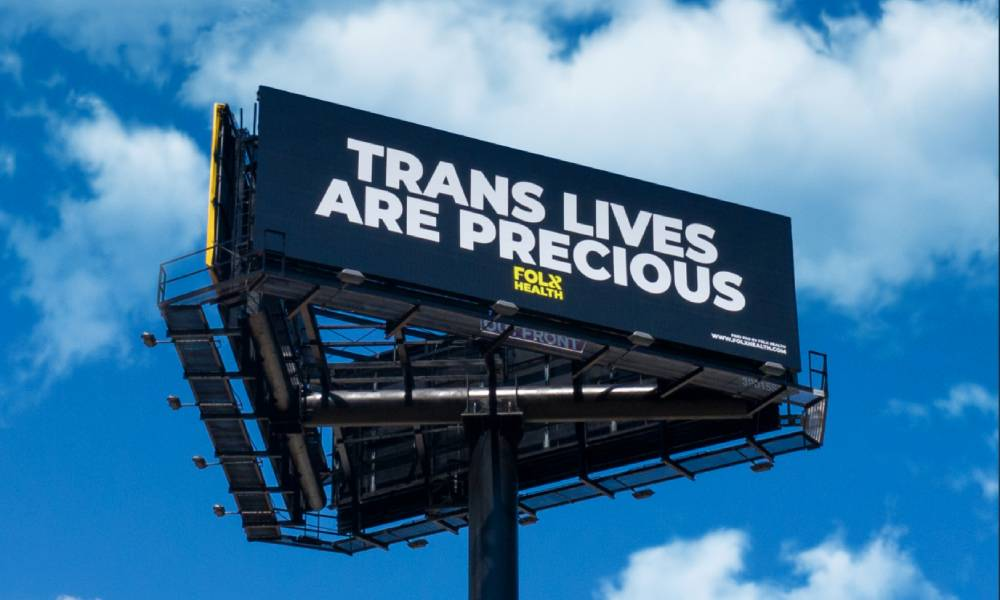 Three billboards in a triangle formation. The front one is visible and reads: Trans lives are precious