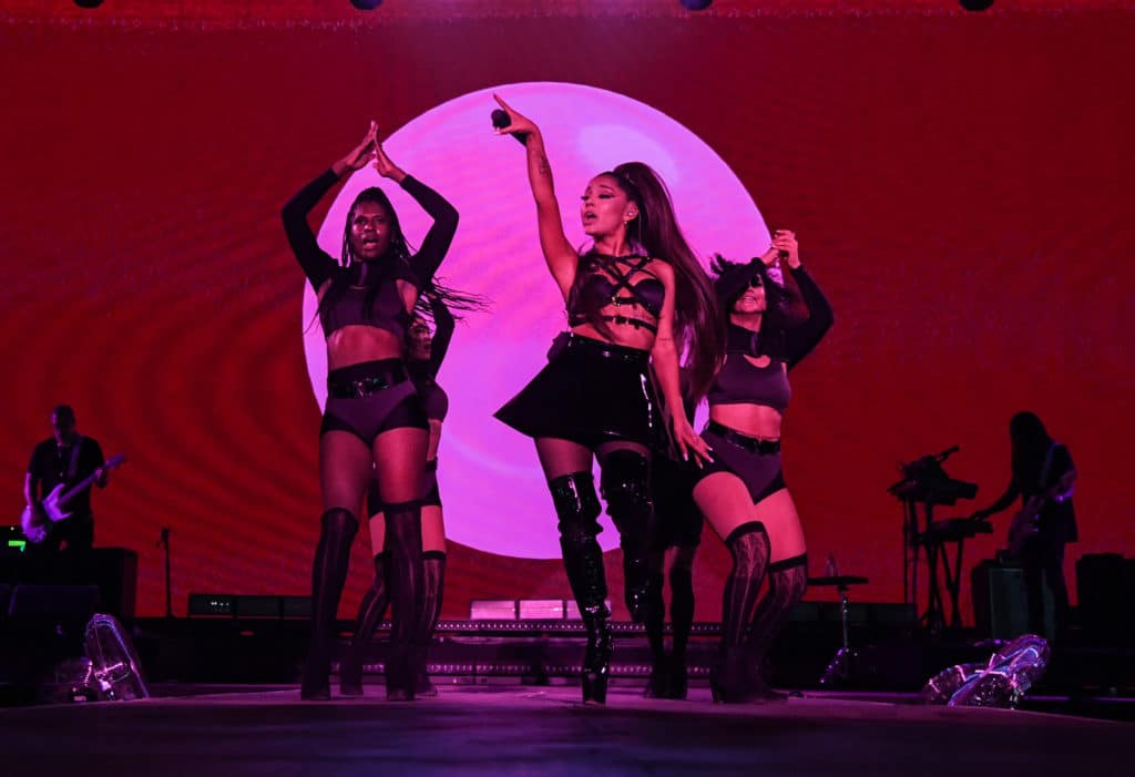 Ariana Grande and dancers on stage, drenched in pink lighting