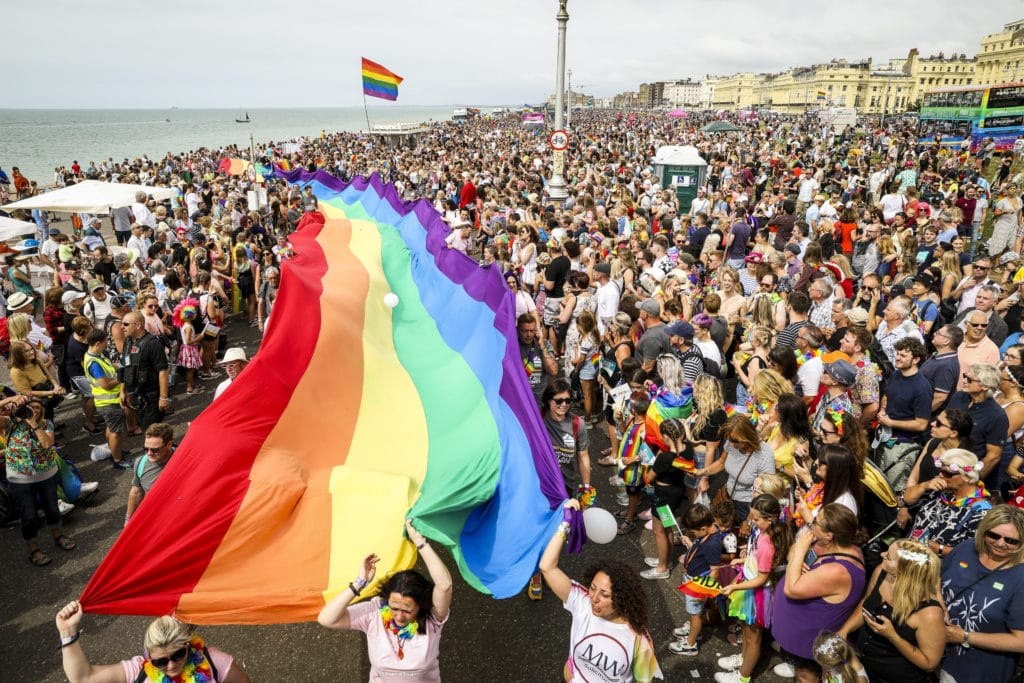 A crowd of pride goers with a giant, long rainbow banner stretching through the crowd