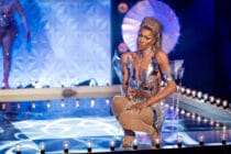 Tayce crouching on the MainStage in a silver metallic costume
