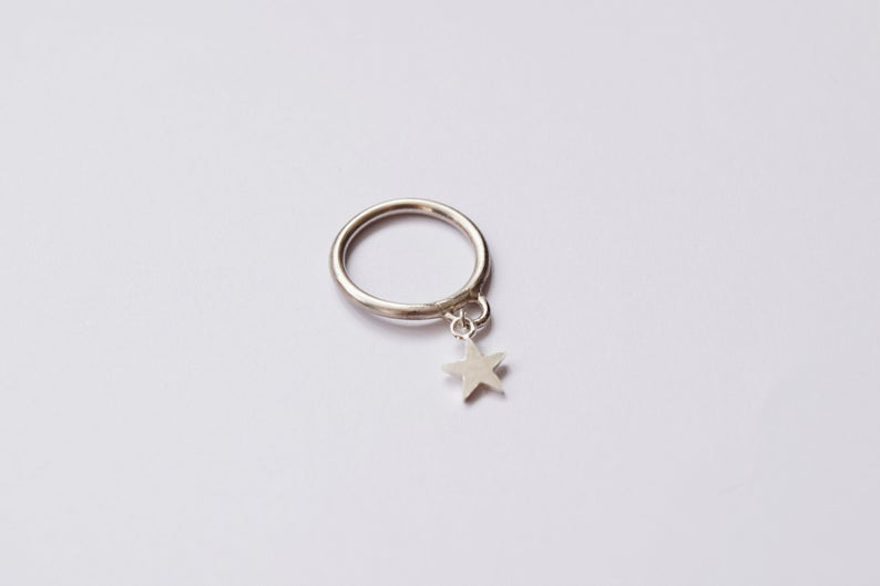 An anxiety ring with a star charm. (3crownsShop)