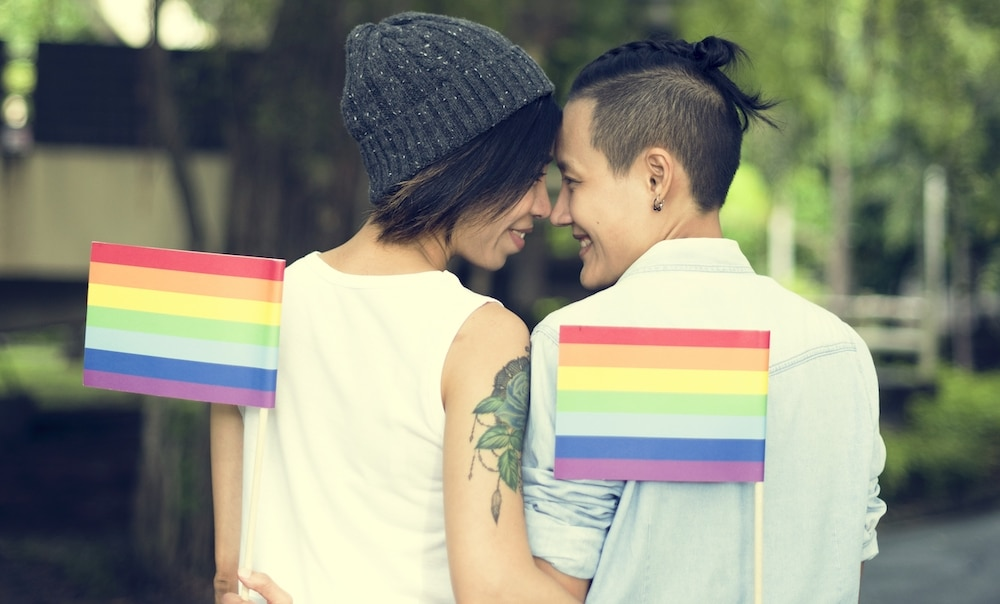 LGBT+ couple holding Pride flags
