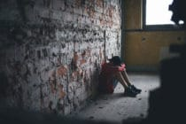 Sad and disappointed teenagers boy sitting indoors in abandoned building