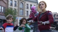 Superheros Wanda and Vision with their two young children, Billy and Tommy, all standing in a street with their hands raised, ready to attack