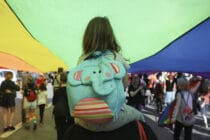 A child facing away from the camera, wearing an elephant backpack