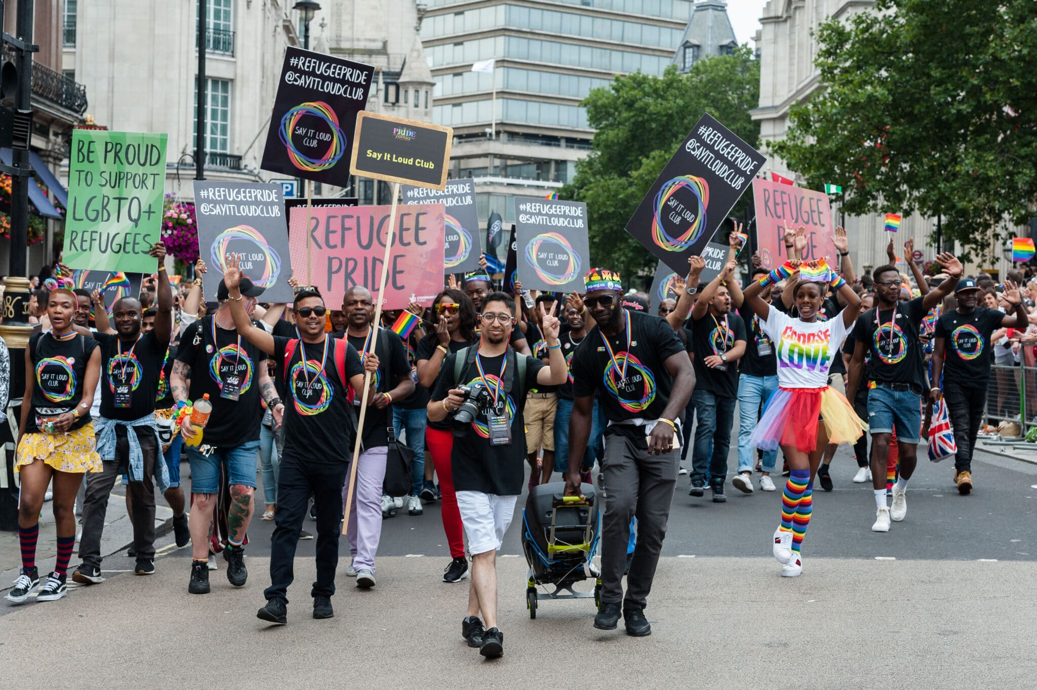 """A crowd of mostly Black and brown LGBT+ protesters holding placards with messages like """"refugee pride"""" and """"be proud to support LGBTQ refugees"""""""