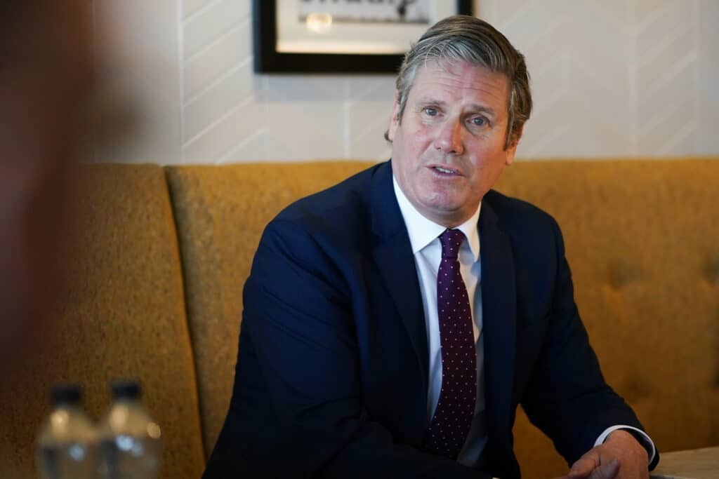 Keir Starmer watches on sat in a cushioned chair wearing a suit