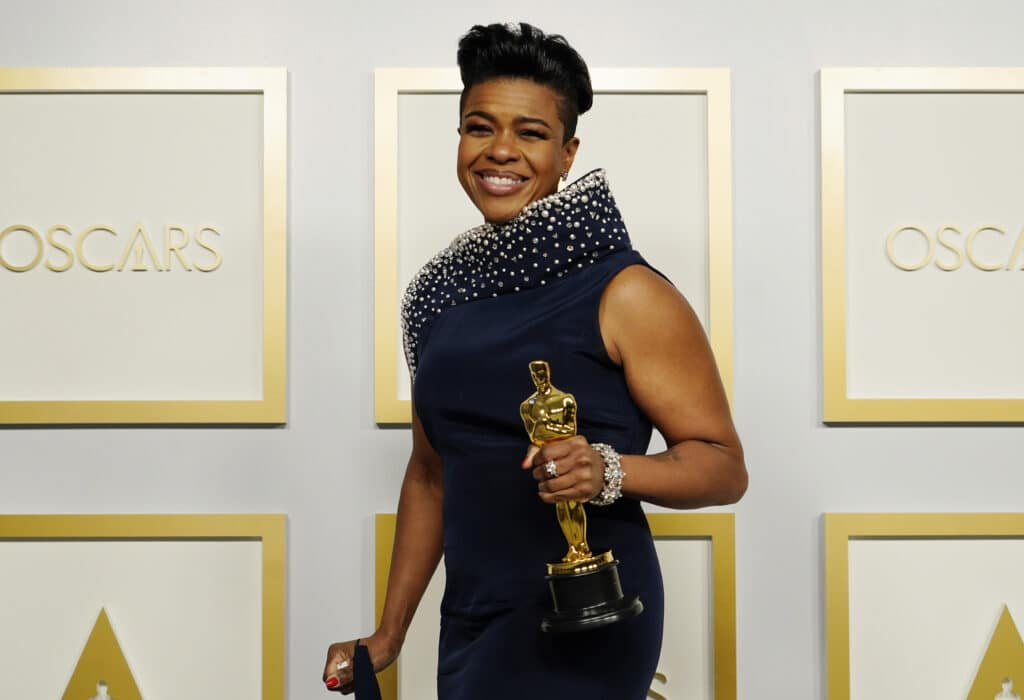 Mia Neal triumphantly holds her Oscar award in a navy dress on the Oscars red carpet