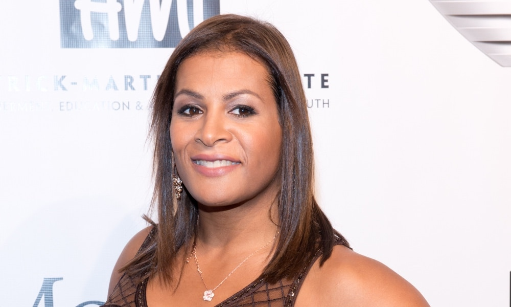 Fallon Fox poses in a brown lace dress