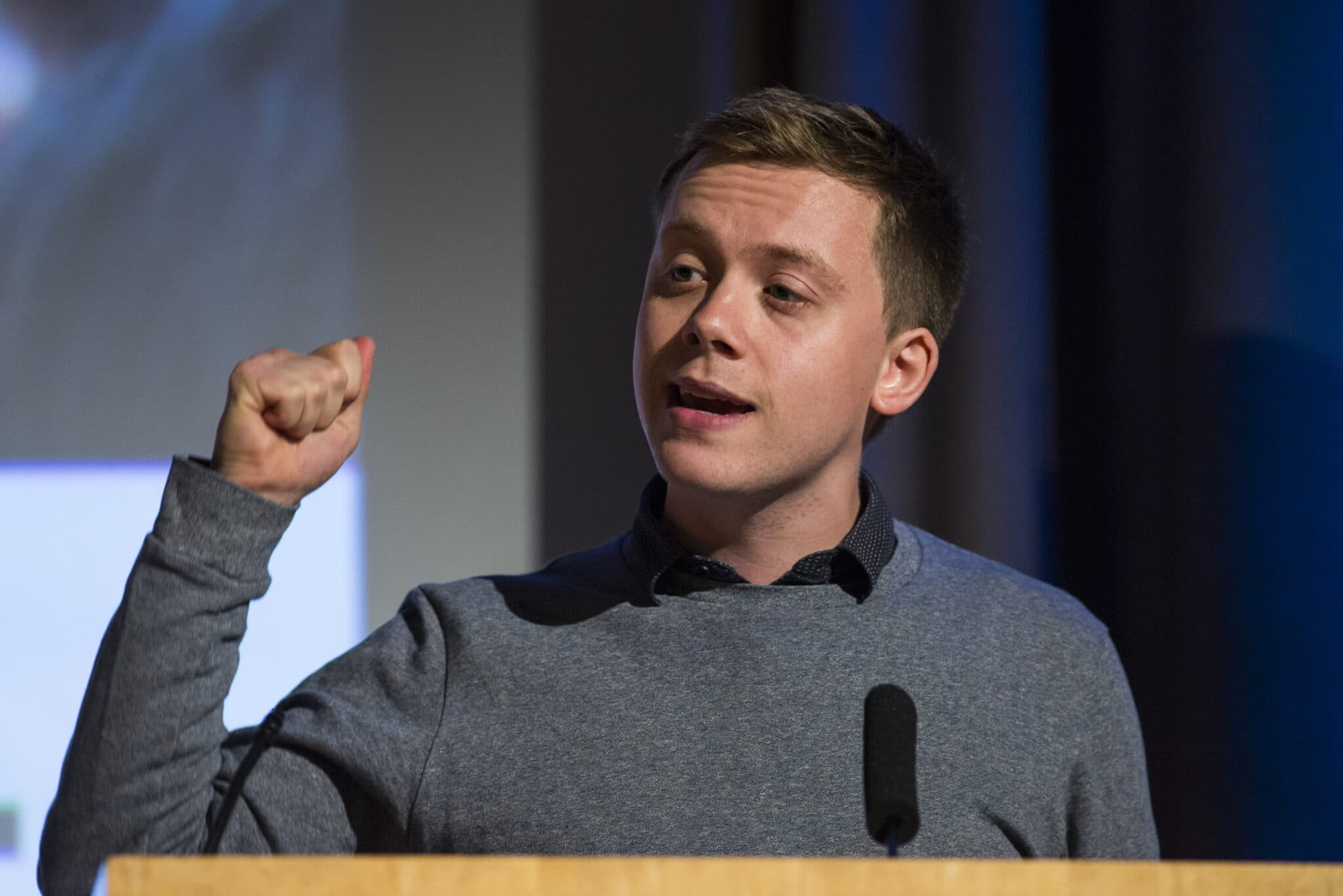 Owen Jones speaks in front of a podium in a grey jumper over a blue shirt