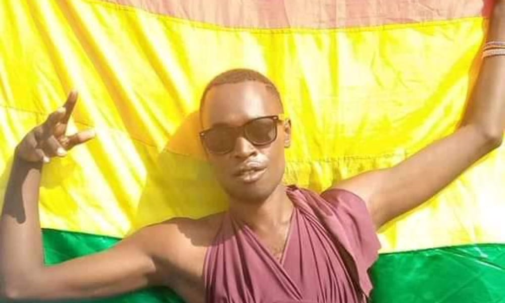 Chriton 'Trinidad Jerry' Atuhwera holds an LGBT+ Pride flag behind him, wearing a pair of sunglasses