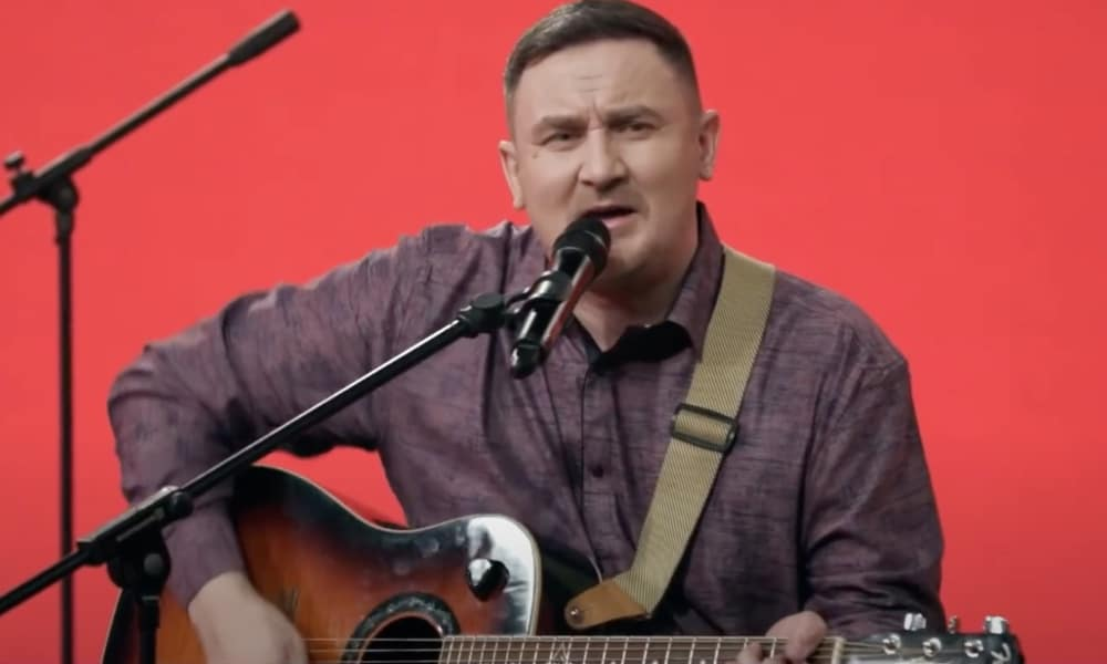 Dmitry Butakov sings while strumming the guitar against a red background