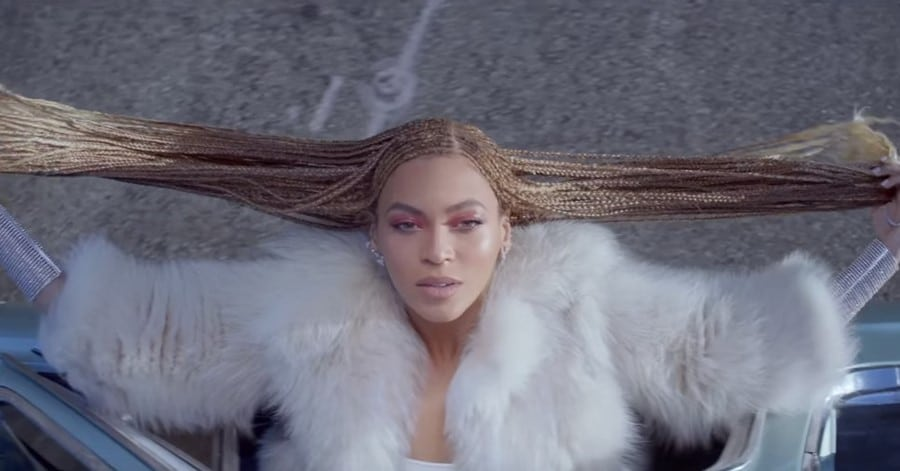 Beyoncé, from above, hanging out of a car window and holding her braids out to the side