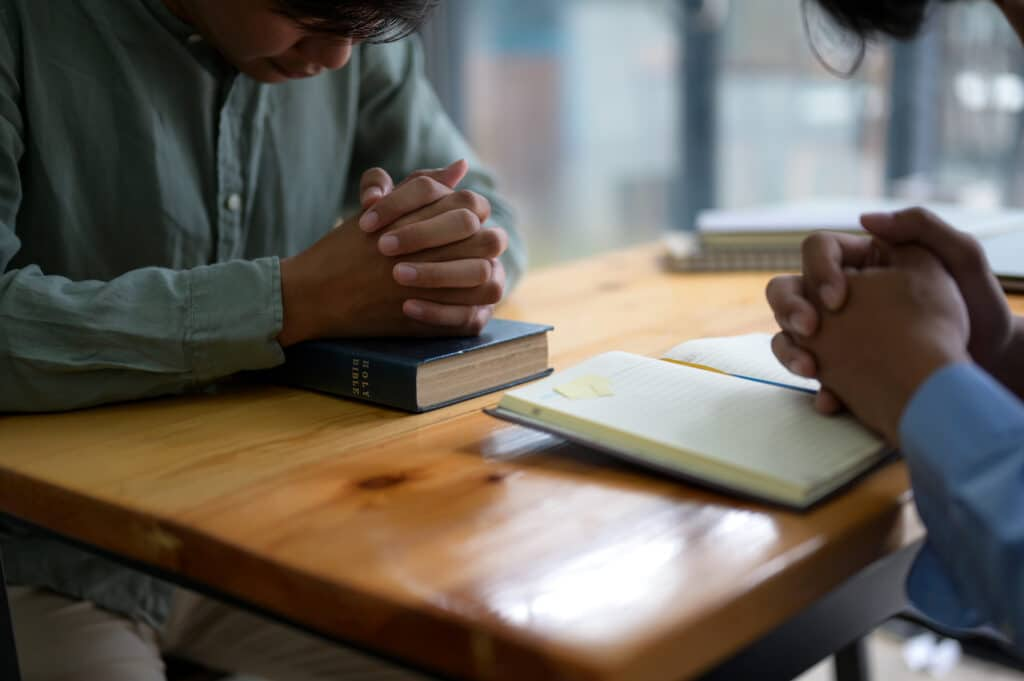 Two people pray with Bibles