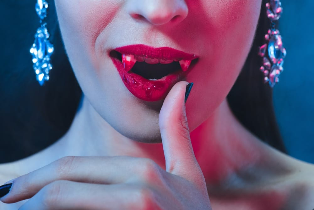 Close-up of a vampire bride wiping blood from her mouth
