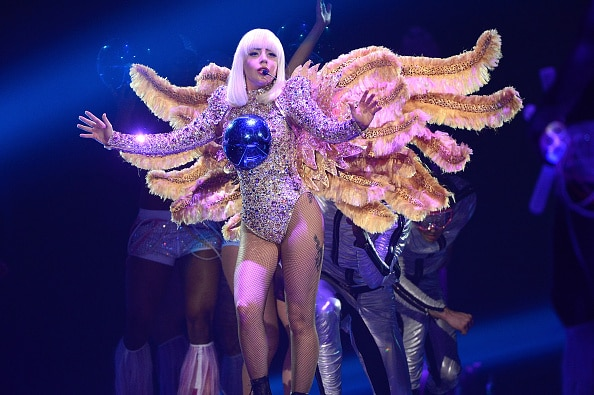 Lady Gaga, wearing a winged costume with a blue ball on her chest, performs onstage during The ARTPOP Ball tour opener