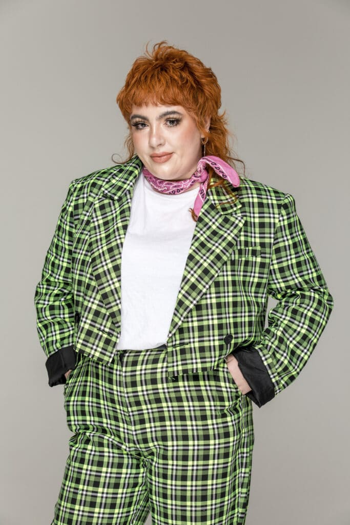 Alex, a woman wearing a green checkered suit with pink hair