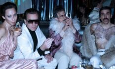 Ewan McGregor as Halston, sat with a woman, a man in a feather boa and another man in a mesh top