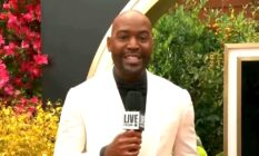 Karamo Brown holds a microphone in a white blazer and black shirt on the Oscars red carpet