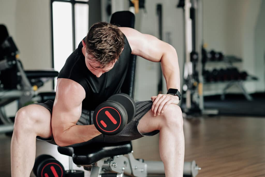 Fit young man working out in gym and doing exercises for biceps