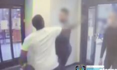 A man in a white tee shirts swings his fist at a man at the entrance of a drugstore