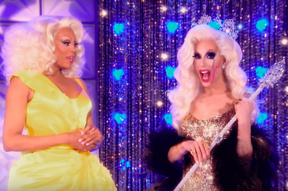 RuPaul standing next to Alaska, who is wearing a crown and holding a sceptre