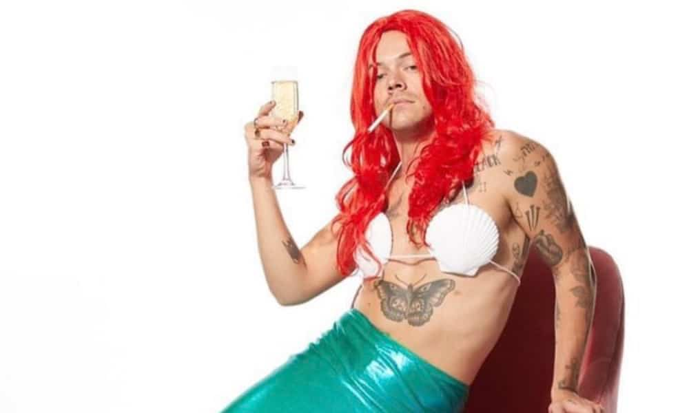 Harry Styles in an Ariel costume, a cigarette in his mouth and holding a flute of champagne