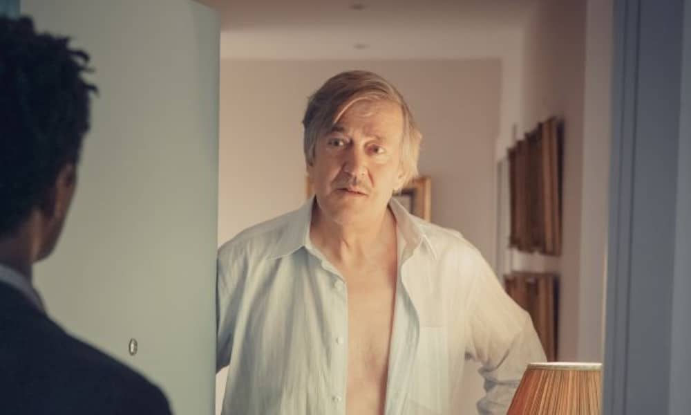 Stephen Fry in It's a Sin, opening the door to someone shirtless