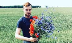 Normunds Kindzulis holds a bouquet of flowers in a field