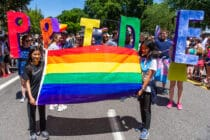 Two girls lead a segment of the parade with a rainbow flag followed by adults with the word 'PRIDE' during the Portland Pride Parade