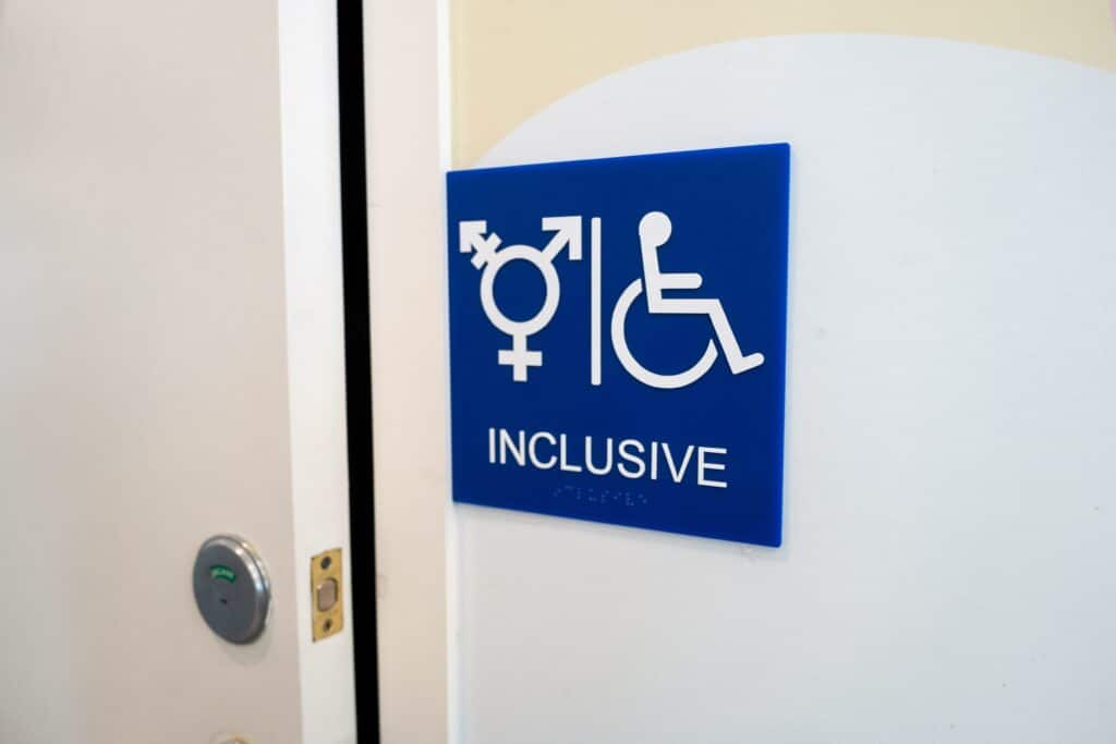 Sign for inclusive restroom, with symbol indicating male, female and transgender as well as handicapped symbol, part of LGBT rights initiatives in the Mission District neighborhood of San Francisco