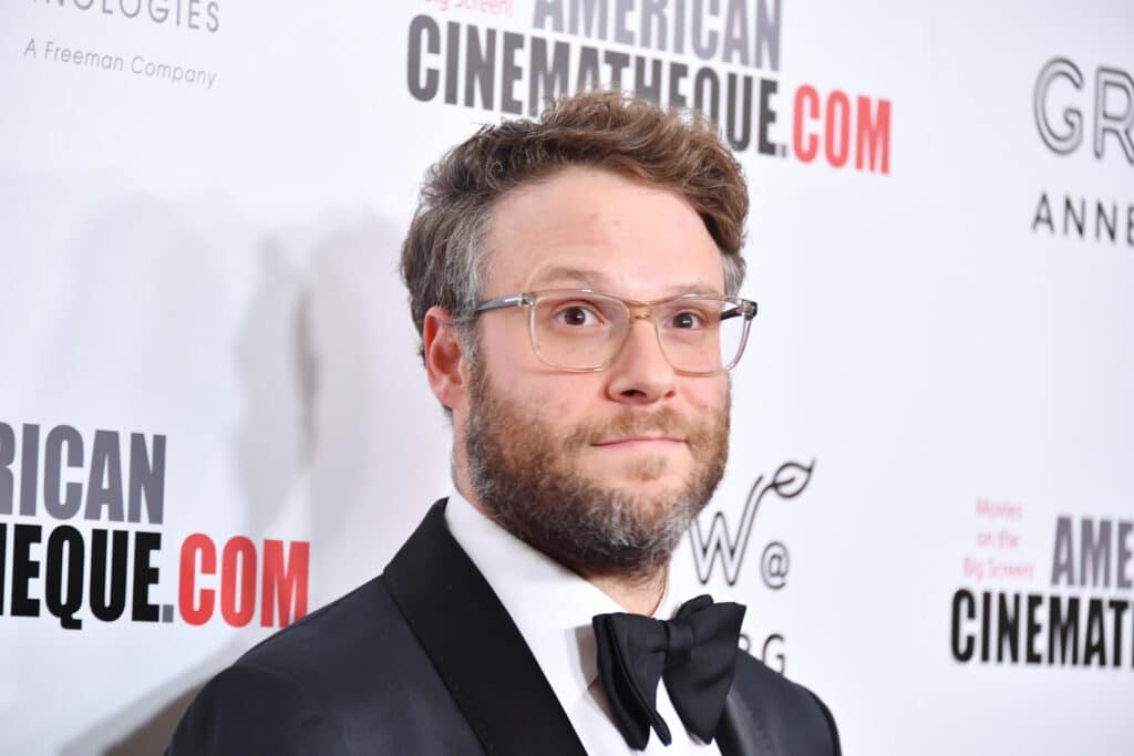 Seth Rogen wearing a tuxedo and a pair of glasses on the red carpet