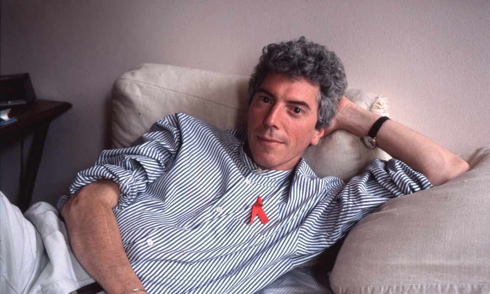 Patrick O'Connell sitting on his bed in a blue shirt and red ribbon