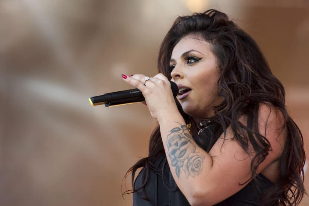 Jesy Nelson sings into the microphone