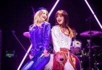 JoJo Desmond and Rhiannon Porter of ABBA MANIA, in costume while singing against one another's backs
