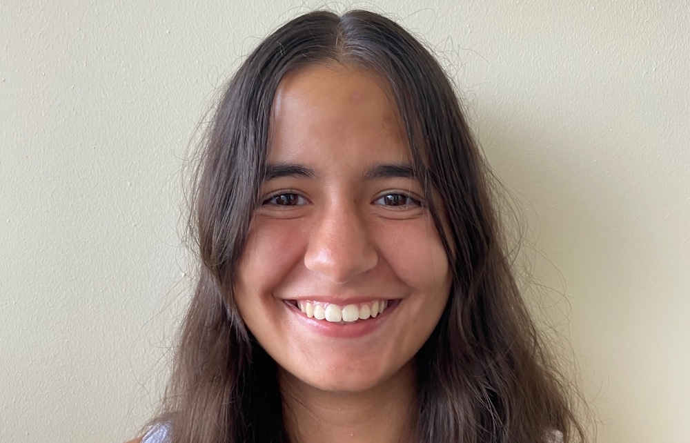 A headshot of Leonor Silva smiling against a grey background