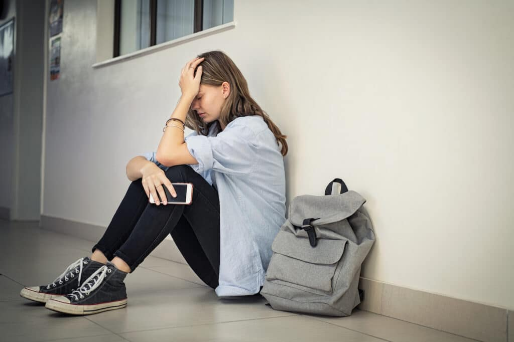 Distressed LGBT+ student targeted by bullies sits with her head in her hands