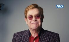 Elton John smiles against a grey background