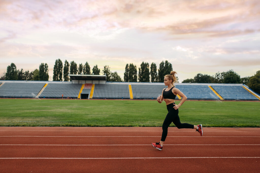 Female runner in sportswear jogging, training on stadium. Woman doing stretching exercise before running on outdoor arena