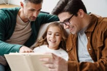 Happy gay parents reading book together with their little daughter at home