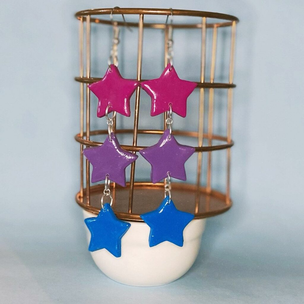 Dangly star earrings in the bi flag colours. (Etsy/librarights)