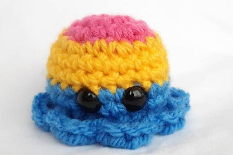 A cute knitted octopus with the pansexual flag colours. (JustBeeYourselfCraft)